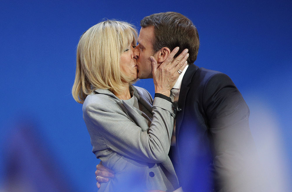 """Лидер движения """"Вперед"""" Эммануэль Макрон победил в первом туре выборов президента Франции – за него проголосовали 23,86% избирателей. Вместе с ним во второй тур, который состоится 7 мая, прошла Марин Ле Пен ( 21,53%). Политологи считают победу Макрона во втором туре фактически предрешенной. А публика обсуждает будущую первую леди (вернее, мадам) Франции. На всех политических мероприятиях рядом с политиком находится его жена, Брижит Тронье. Будущие супруги познакомились в школе: Тронье преподавала французский язык, а Макрон влюбился в учительницу. Она, мать троих детей, развелась с мужем и уехала с Макроном в Париж. Несмотря на разницу в возрасте - Тронье старше Макрона на 24 с лишним года - они поженились, когда ему исполнилось тридцать. Сейчас Брижит 64 года, у нее семеро внуков (Эммануэль помогает их воспитывать), Макрону - 39 лет. Брижит находится в отличной форме - у нее девичья фигура."""