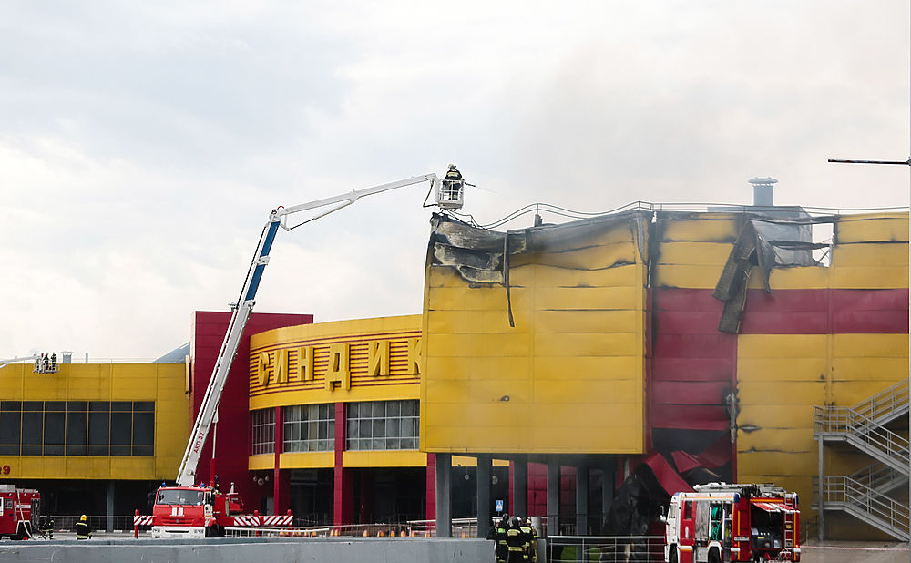 """Угроза обрушения конструкций сохраняется в торговом центре """"Синдика"""" на 65-м км МКАД в Одинцовском районе. Пожар начался днем в воскресенье: загорелись склады рядом с подземной парковкой. По словам пожарных, температура была настолько высокой, что конструкции оплавились и разрушились полностью. Огонь разгорелся на площади 150 тыс. кв.м, пострадали три человека. Ущерб от пожара в ТЦ может составить около 5 млрд рублей, уже выяснилось, что здание было застраховано на сумму 4,2 млрд рублей."""