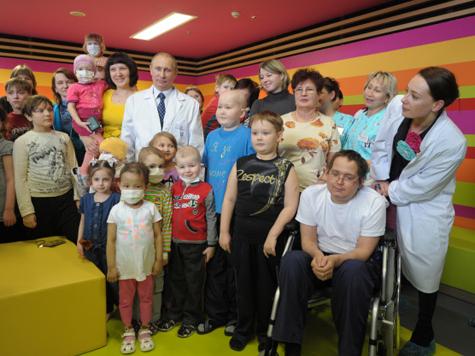 Владимир Путин (в центре) с пациентами и их  родителями во время посещения Федерального научно-клинического центра  детской гематологии, онкологии и иммунологии имени Димы Рогачева. Справа  - соучредитель фонда